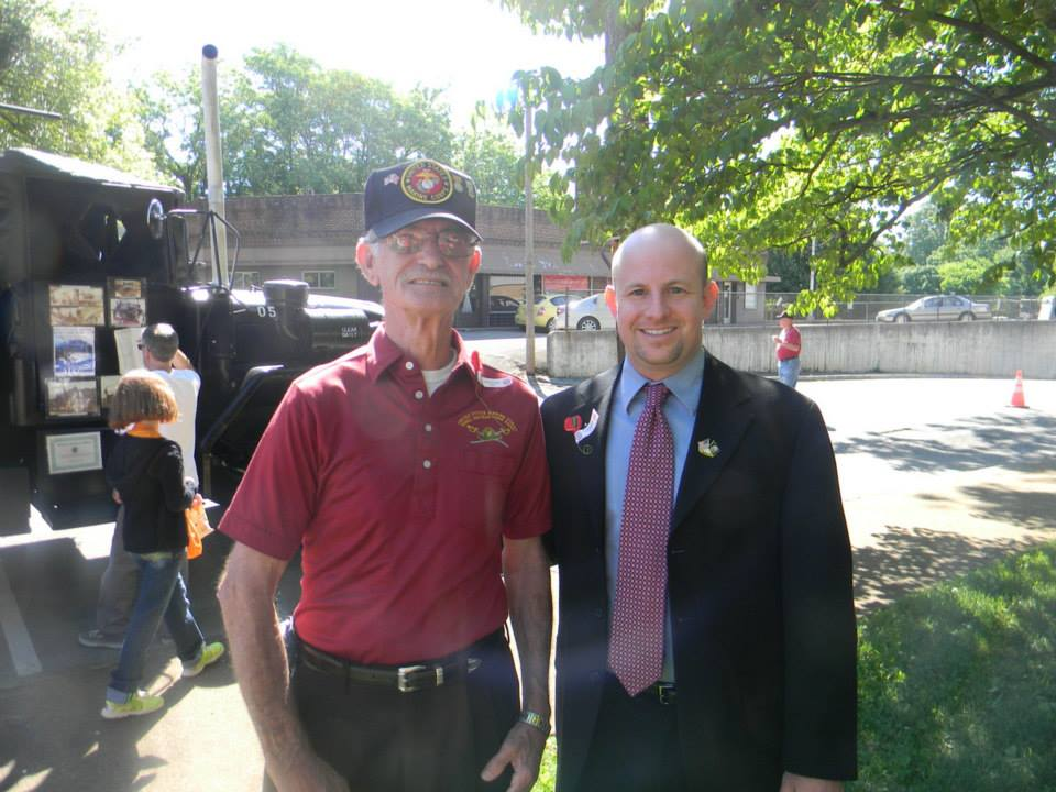 Image of veteran in red shirt, standing with man in suit
